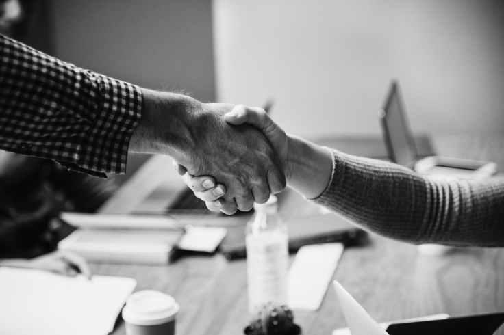 grayscaled photo of handshake